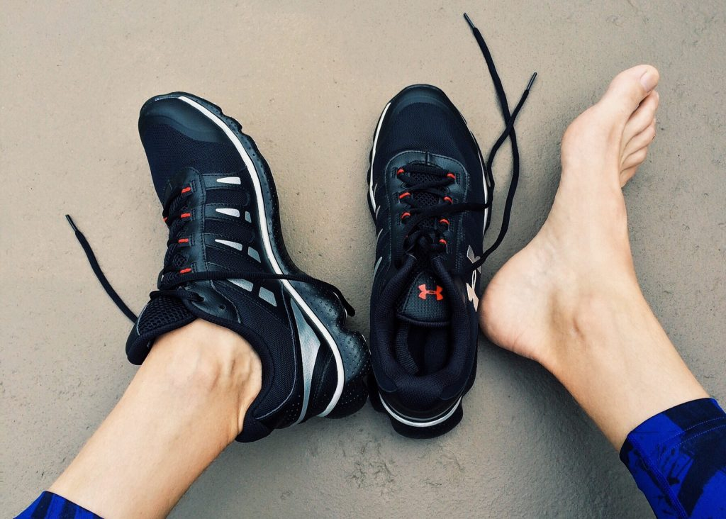 overhead photo of person's feet - one foot wearing runners, the other barefoot